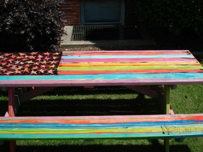 "Among other artists, Nicole Lamar will paint an Adirondack rocker that will be auctioned in the Double Decker Picnic Area. Last year she painted this table, titled ""Oh, Say, Can You See?"" pictured here."