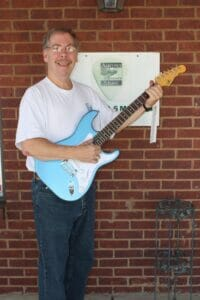Austin's Music owner Kenneth Lacy with the G&L guitar that will be raffled.