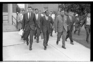 James Meredith walks to class surrounded by protesters, journalists, and armed guards.