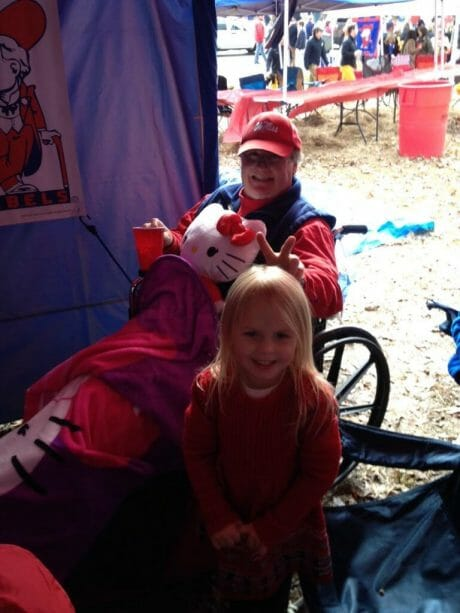 Members of the McCullough tailgating group always have a great time in the Grove. Here, Ashlynn Waddell takes care of Ron Knapp by letting him play with her Hello Kitty items.