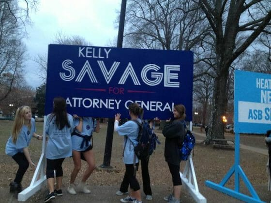 Kelly Savage supporters attempt to move her campaign sign.