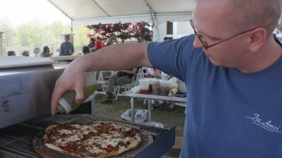 Richard Traylor of Tre Amici puts the finishing touches on his pizza.
