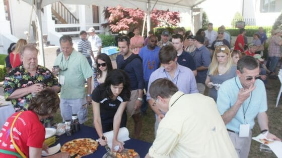 People line up to sample the pizza.
