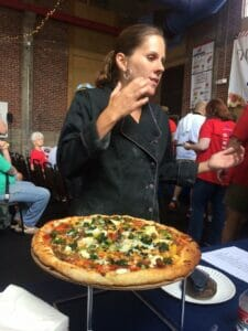 Karen Irby explains to judges that campers at Camp Lake Stephens grow all the toppings for her pizza.