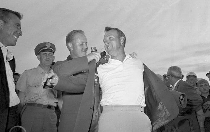 Arnold Palmer slips into a green coat, the traditional symbol of the Masters Golf winners, in ceremony at Augusta on April 12, 1964, after a record fourth victory for the Pennsylvania professional.