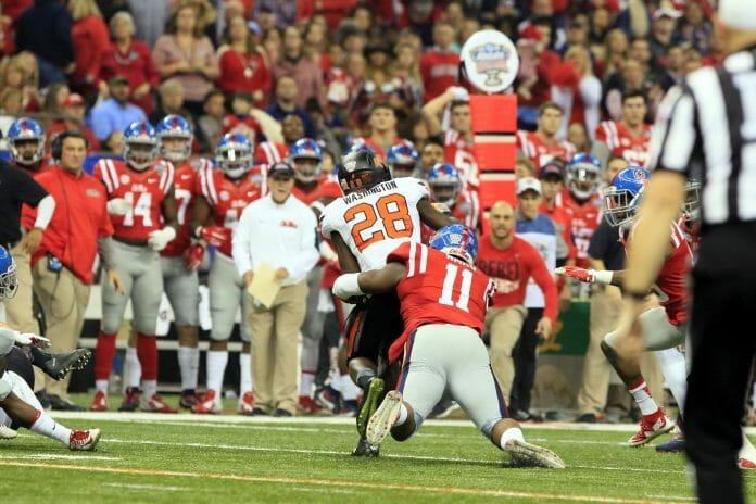 Channing Ward tackles Cowboys' James Washington. Photo by John Bowen.