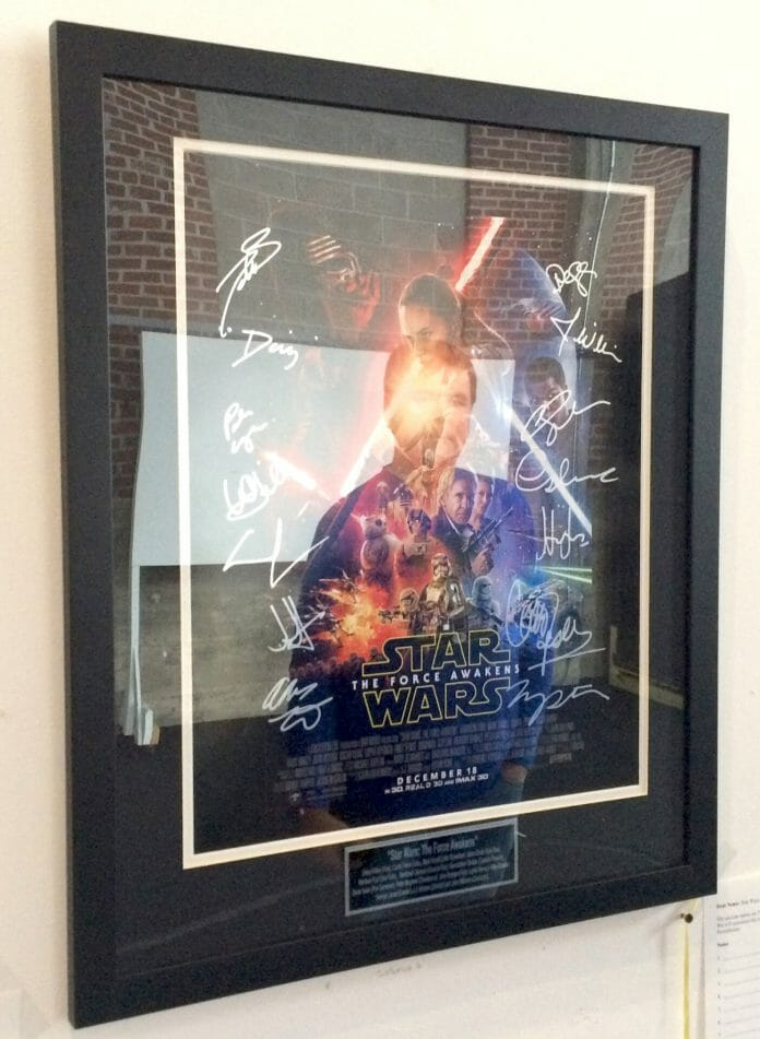 Memphian Richard Warren's reflection can be seen in the middle of the 'Star Wars' poster he won at Oxford Film Festival's silent auction being held right now (through Sunday) at the Powerhouse. Photo by Jeff McVay