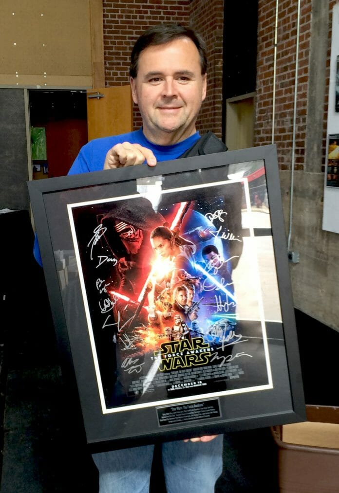 Memphian Richard Warren shows the 'Star Wars: The Force Awakens' autographed poster he won at OFF's silent auction being held at the Powerhouse. Photo by Jeff McVay
