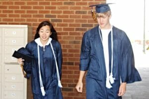 Mullen and Chen try on graduation gowns for OHS.